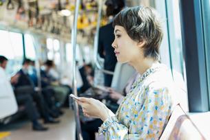 電車で音楽を聴く女性の写真素材 [FYI01820445]