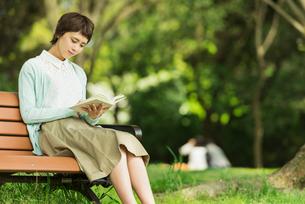 公園で読書する若い女性の写真素材 [FYI01820500]