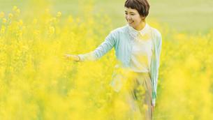 菜の花畑を散歩する女性の写真素材 [FYI01820523]