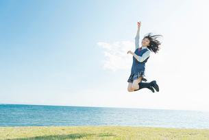 女子高生 海 草原 ジャンプの写真素材 [FYI01820529]