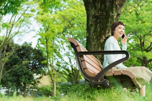 公園で電話する若い女性の写真素材 [FYI01820560]