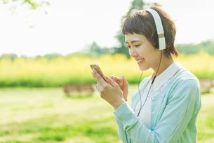 公園で音楽を聴く女性の写真素材 [FYI01820572]