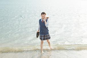 女子高生 海 裸足 スマホ通話の写真素材 [FYI01820588]