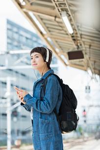 ホームで音楽を聴きながら電車を待つ女性の写真素材 [FYI01820595]