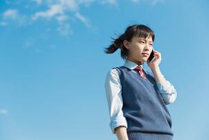 女子高生 青空 スマホの写真素材 [FYI01820638]