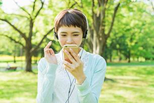 公園で音楽を聴く女性の写真素材 [FYI01820736]