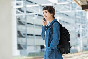 ホームで音楽を聴きながら電車を待つ女性の写真素材 [FYI01820818]