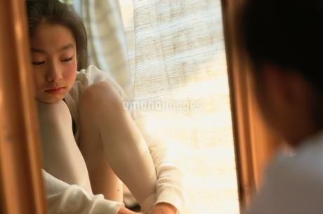 足を抱えて座る日本人の女の子の写真素材 [FYI01820878]