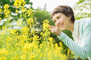 菜の花畑を散歩する女性の写真素材 [FYI01820884]