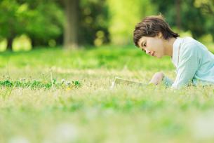 公園の芝生で読書をする女性の写真素材 [FYI01820885]