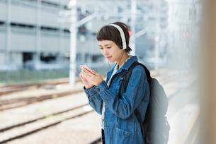 ホームで音楽を聴きながら電車を待つ女性の写真素材 [FYI01820890]