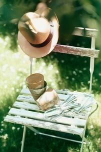 庭のイスにガーデニンググッズと帽子の写真素材 [FYI01821074]