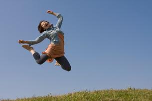 土手でジャンプをする女性の写真素材 [FYI01821131]