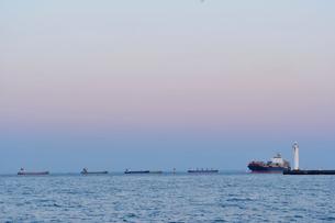 ビーナスベルトが見える海に白灯台とコンテナ船の写真素材 [FYI01821147]