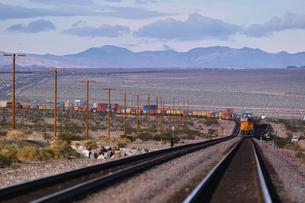砂漠地帯を走る貨物列車の写真素材 [FYI01821211]
