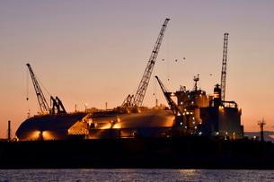 夕日に浮かびあがる船のドッグとクレーンの写真素材 [FYI01821223]