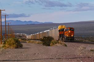 砂漠地帯を走る貨物列車の写真素材 [FYI01821276]