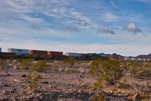 砂漠地帯を走る貨物列車の写真素材 [FYI01821314]