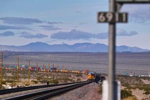 砂漠地帯を走る貨物列車の写真素材 [FYI01821589]