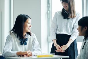休み時間に教室で雑談する女子高校生の写真素材 [FYI01822561]