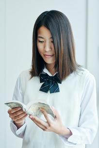 窓際で本を読む女子高校生の写真素材 [FYI01822590]