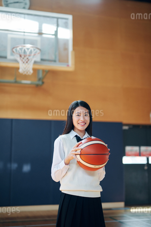 体育館でバスケットボールを持つ女子高生の写真素材 [FYI01822600]