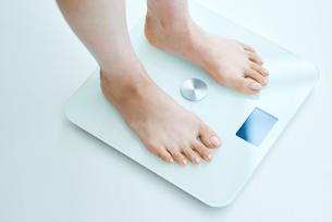 体重計に足を乗せる女性の写真素材 [FYI01822609]