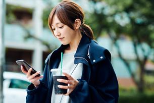 アイスコーヒーを飲みながらスマートフォンをチェックする若い女性の写真素材 [FYI01822693]