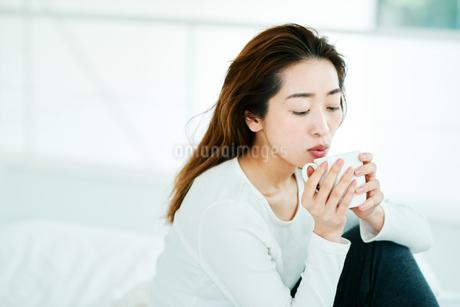 温かい飲み物を飲む女性の写真素材 [FYI01822694]
