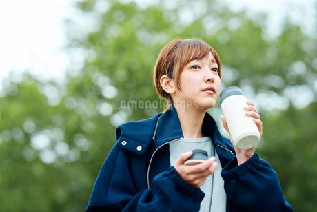 温かい飲み物を飲む若い女性の写真素材 [FYI01822719]