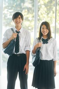 カバンを持って並んで立つ笑顔の男女の高校生の写真素材 [FYI01822723]