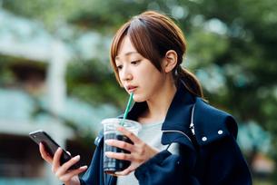 アイスコーヒーを飲みながらスマートフォンをチェックする若い女性の写真素材 [FYI01822735]