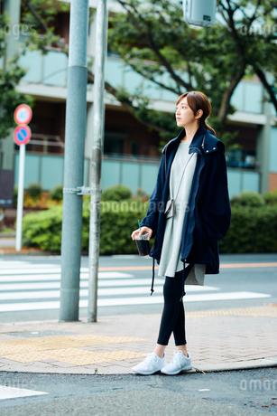 街中で立ち止まる若い女性の写真素材 [FYI01822749]