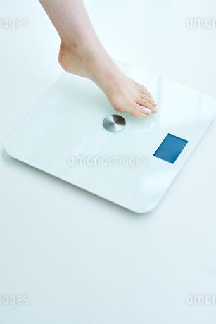 体重計に足を乗せる女性の写真素材 [FYI01822761]