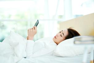 ベッドの上でスマートフォンをチェックする女性の写真素材 [FYI01822770]