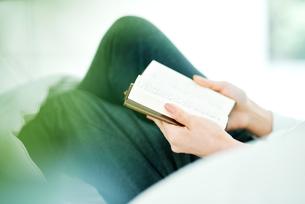 ベッドの上で読書をする女性の写真素材 [FYI01822786]