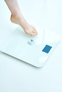 体重計に足を乗せる女性の写真素材 [FYI01822791]
