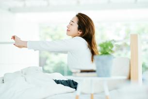 ベッドの上でリラックスする女性の写真素材 [FYI01822792]