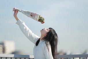 屋上でドライフラワーを掲げる女性の写真素材 [FYI01822807]