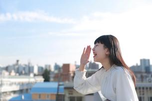 屋上で手を口の前に添えて叫ぶ女性の写真素材 [FYI01822816]