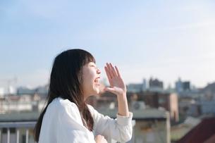 屋上で手を添えて叫ぶ女性の写真素材 [FYI01822885]
