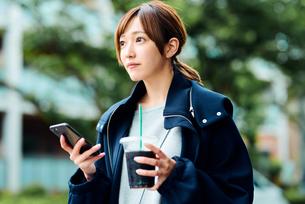 アイスコーヒーを飲みながらスマートフォンをチェックする若い女性の写真素材 [FYI01822916]