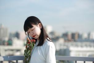 屋上でドライフラワーの匂いを嗅ぐ女性の写真素材 [FYI01822977]