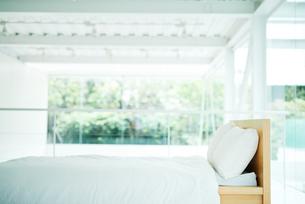 大きな窓のある白い部屋に置かれたベッドの写真素材 [FYI01823013]