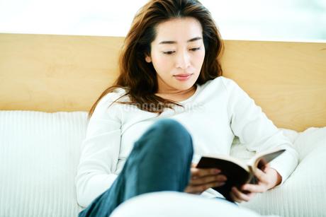 ベッドの上で読書をする女性の写真素材 [FYI01823017]