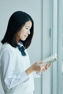 窓際で本を読む女子高校生の写真素材 [FYI01823032]