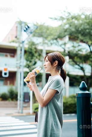 デトックスウォーターで水分補給をする若い女性の写真素材 [FYI01823070]