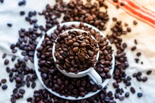 コーヒーカップから溢れるコーヒー豆の写真素材 [FYI01823073]