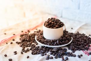 コーヒーカップから溢れるコーヒー豆の写真素材 [FYI01823099]