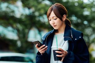 アイスコーヒーを飲みながらスマートフォンをチェックする若い女性の写真素材 [FYI01823153]